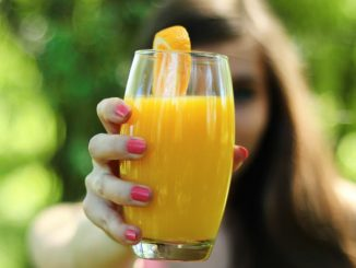 holding glass of juice