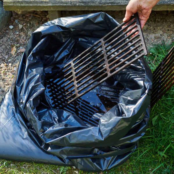 placing grill grates into a garbage bag